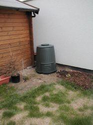 Foto: Der grüne, runde Komposter in der Ecke am Gartenhaus