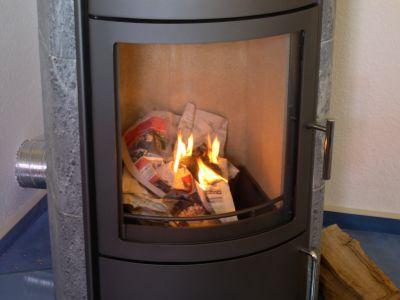 Brennendes Zeitungspapier im Kaminofen