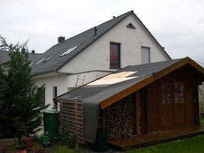 Gartenhütte mit herabhängender Dachpappe