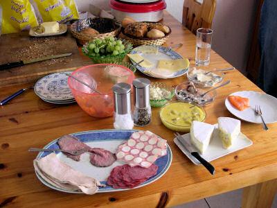 Brötchen, Platten mit Wurst und Käse, Schälchen mit eingelegtem Fisch