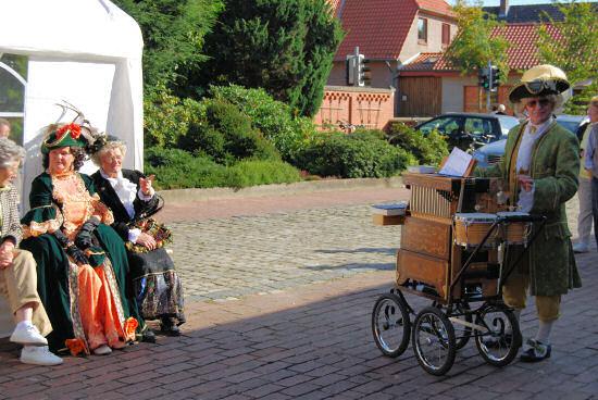 Drehorgelspieler und zwei Damen in altertümlichen Kostümen