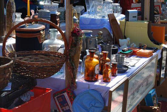 Tisch auf dem Flohmarkt mit Glasflaschen, Geschirr, Bildern etc.