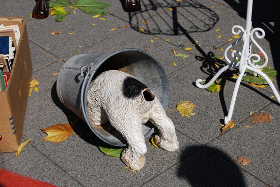 Plastikhund mit Kopf in einem umgestürzten Eimer