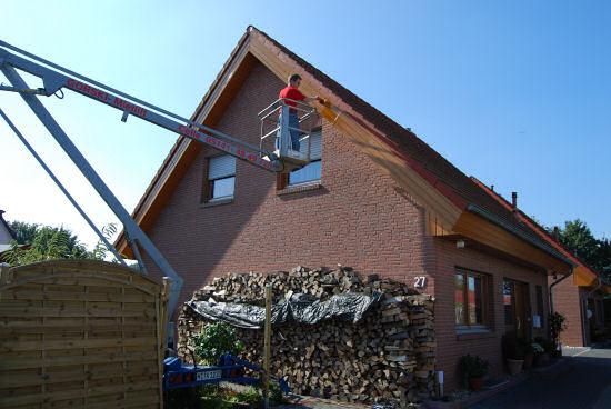 Mann streicht Holz am Dach im Hubsteiger