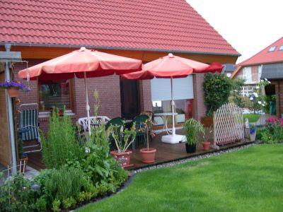 zwei aufgespannte rote Sonnenschirme auf der Terrasse