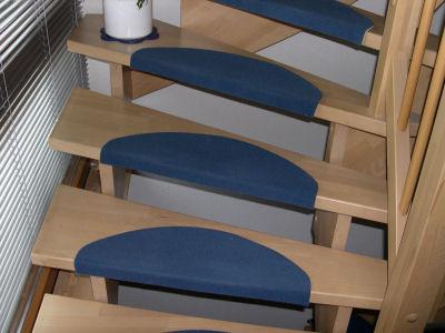 Holztreppe mit blauen Stufenmatten